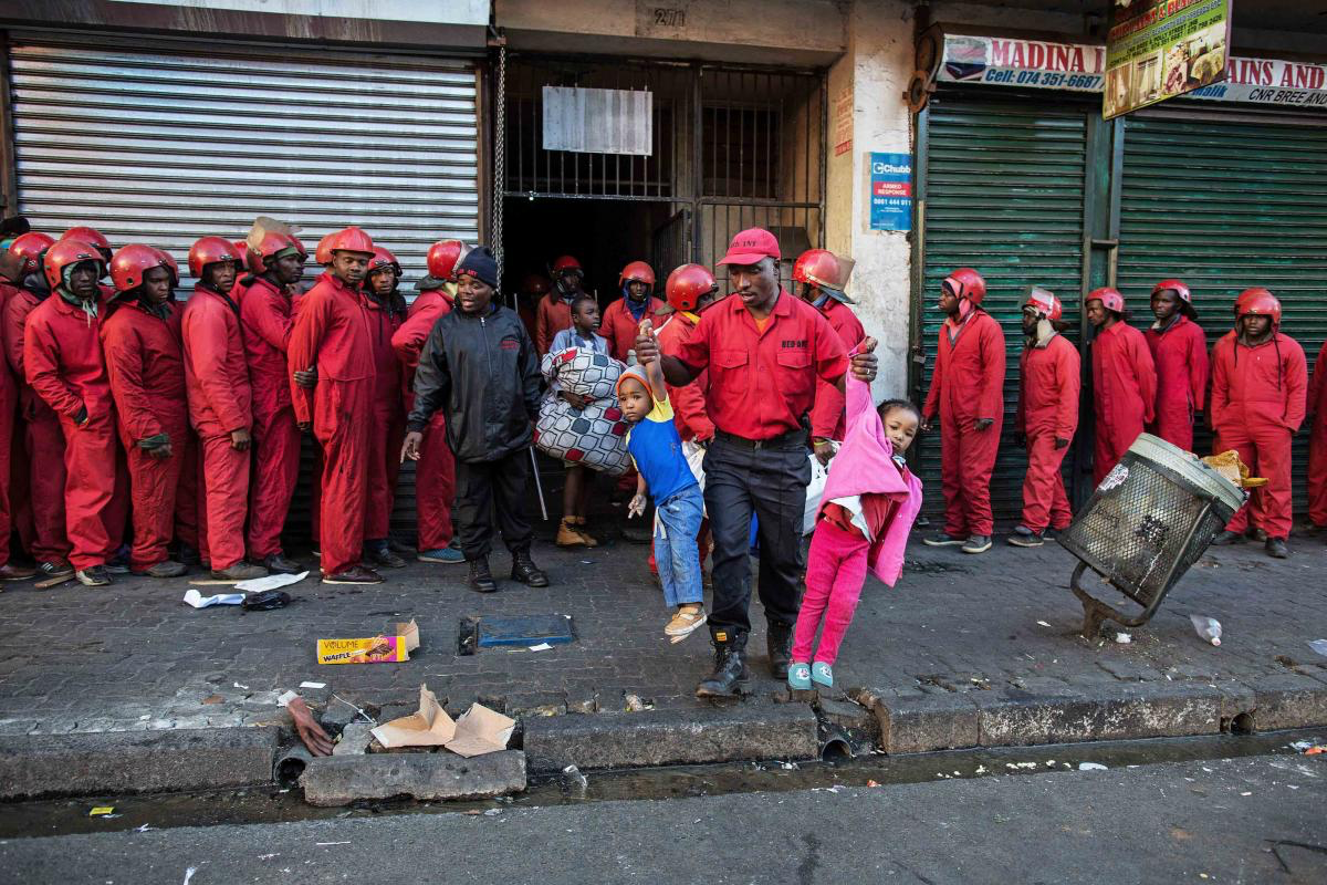 23 June 2017. A Red Ants major carries out two small children during the eviction of residents of a so-called hijacked building in Bree Street, Johannesburg.