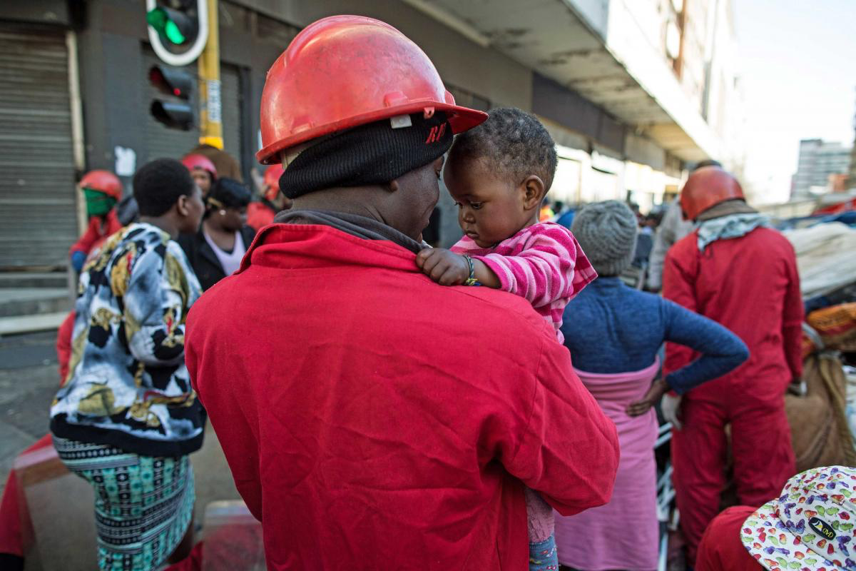 19 July 2017: Red Ant William Mahlalela plays with S'nehlanhla Fortunate Majoro while her mother tried to gather together some belongings after they were evicted from Fatti's Mansions in Johannesburg.