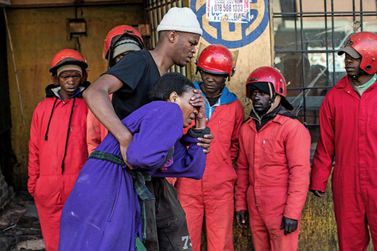 6 June 2017. Catherine Mathebula breaks down as her son Kenny escorts her from the hijacked building where they lived in Bree Street, Johannesburg. A few weeks later they were evicted again from another building.